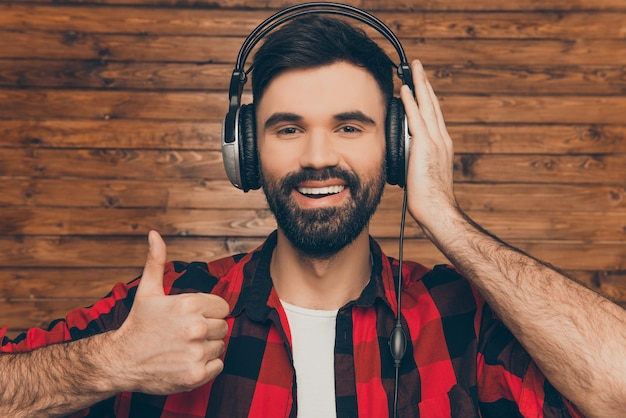 Szczęśliwy człowiek w słuchawkach słuchanie muzyki i pokazywanie kciuka