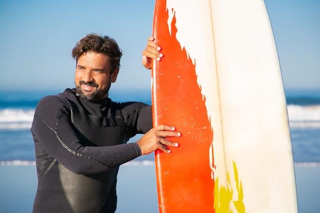Szczęśliwy człowiek w stojący strój kąpielowy z deską surfingową i odwracając. kaukaski brodaty surfer pochylony do deski i uśmiechnięty