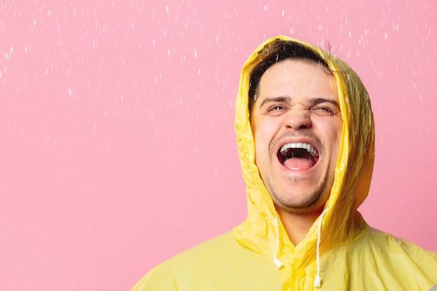 Szczęśliwy człowiek w żółtym płaszczu przeciwdeszczowym na różowej ścianie