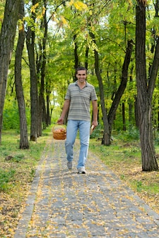 Szczęśliwy człowiek w zwykłym ubraniu idący utwardzoną leśną ścieżką niosący kosz jabłek