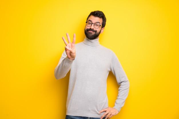 Szczęśliwy człowiek z brodą i golfem i liczący trzy palcami
