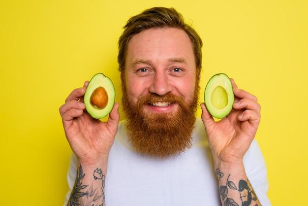 Szczęśliwy człowiek z brodą i tatuażami trzyma awokado