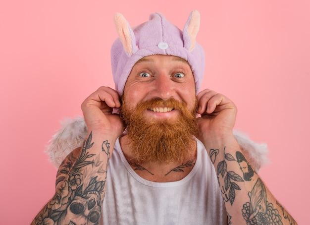 Szczęśliwy człowiek z brodą i tatuażami zachowuje się jak anioł