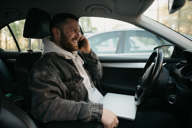 Szczęśliwy człowiek z brodą prowadzący interesy dzwoni na smartfonie w samochodzie, na kolanach leży laptop. uśmiechnięty facet zatrzymał samochód, aby natychmiast zdalnie rozwiązać zadania w pracy w dystansie towarzyskim.