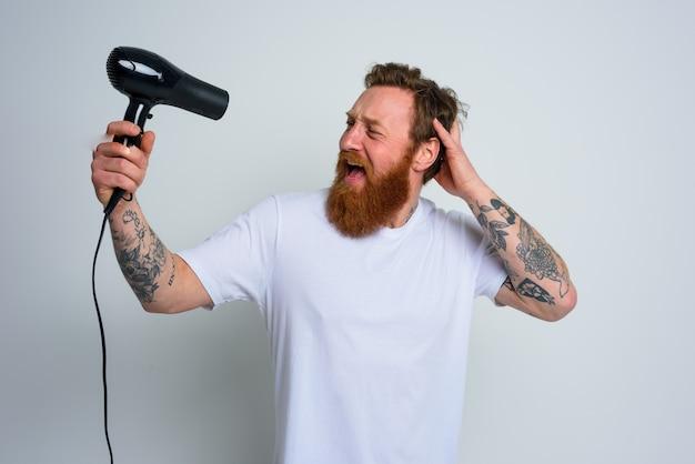 Szczęśliwy człowiek z brodą używa suszarki do włosów jako mikrofonu i tańczy