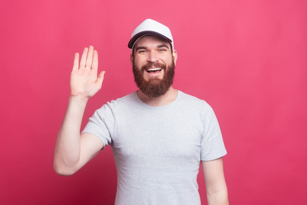 Szczęśliwy człowiek z brodą w kapeluszu i przywitanie