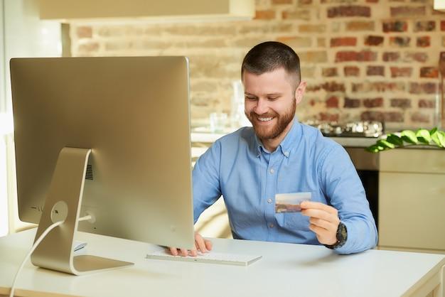 Szczęśliwy człowiek z brodą wpisuje informacje o karcie kredytowej, aby robić zakupy online w domu