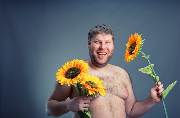 Szczęśliwy człowiek z bukietem słoneczników, odizolowany na szaro