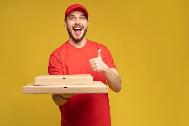 Szczęśliwy człowiek z dostawy w czerwonej koszulce i czapce, dając zamówienie na jedzenie i trzymając pudełko pizzy na białym tle nad żółtą ścianą