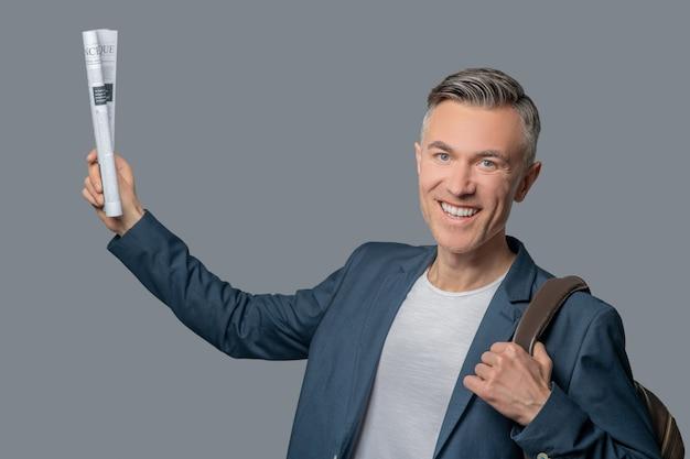 Szczęśliwy człowiek z gazetą w podniesionej dłoni