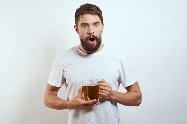 Szczęśliwy człowiek z kubkiem piwa alkoholowego w jego ręce