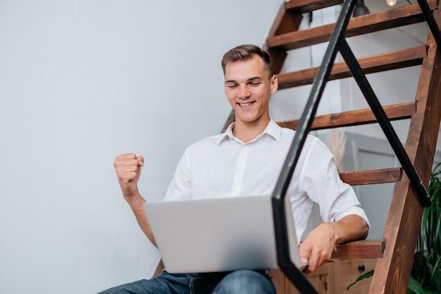 Szczęśliwy człowiek z laptopem siedzący na schodach w swoim mieszkaniu.