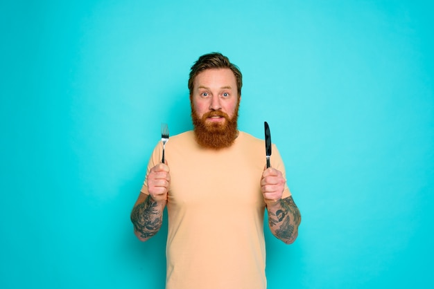 Szczęśliwy człowiek z tatuażami jest gotowy do jedzenia ze sztućcami w ręku