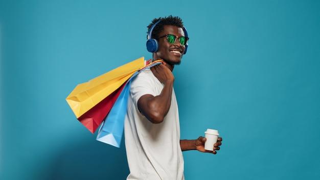 Szczęśliwy człowiek z torebkami tańczącymi po zakupach