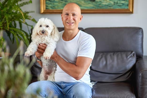Szczęśliwy człowiek z uroczym psem w domu na kanapie