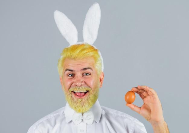 Szczęśliwy człowiek z uszami królika trzyma pisanka na szarym tle.