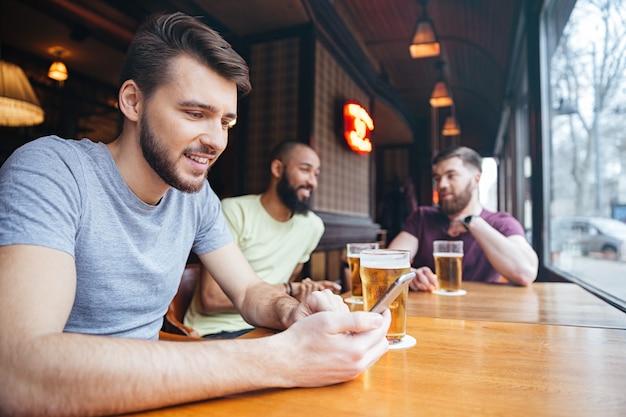 Szczęśliwy człowiek za pomocą smartfona, podczas gdy przyjaciele rozmawiają na tle w pubie piwnym