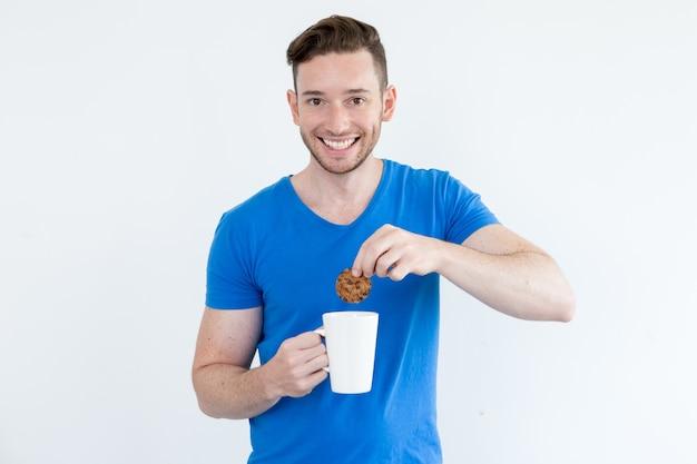 Szczęśliwy człowiek zanurzanie ciasteczka w ciepły napój