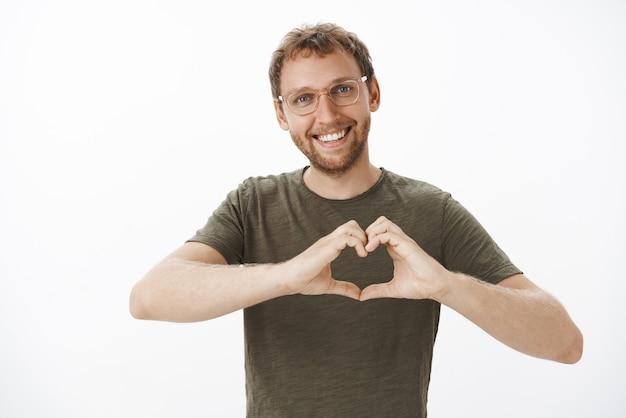 Szczęśliwy, czuły i romantyczny europejski mąż w ciemnozielonej koszulce i okularach uśmiechnięty szeroko, pokazujący gest serca na piersi, okazujący miłość i uczucia
