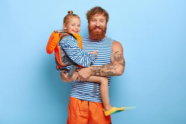 Szczęśliwy, czuły ojciec niesie na rękach małą córeczkę, która nosi ochronną kamizelkę ratunkową i płetwy, idzie razem pływać, cieszyć się latem, mieć rude włosy. ruda rodzina na wakacjach