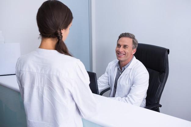 Szczęśliwy dentysta i kobieta rozmawia w kabinie