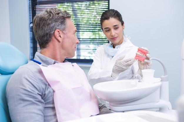 Szczęśliwy dentysta pokazuje człowiekowi pleśń dentystyczną