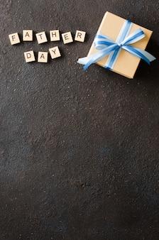 Szczęśliwy dnia ojca kartka z pozdrowieniami z dekorującym prezenta pudełkiem na ciemnym tle.