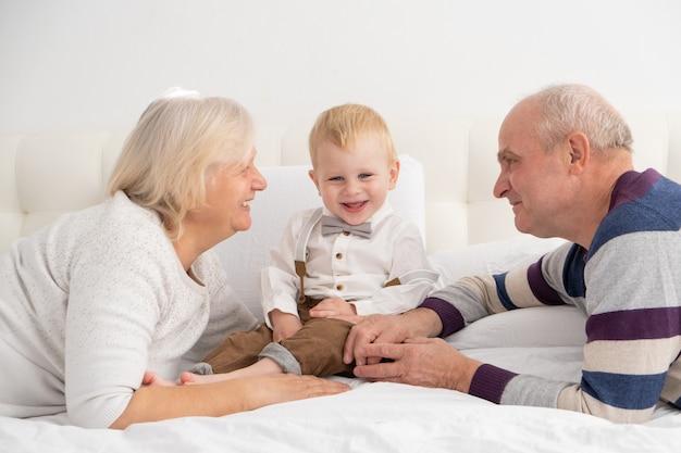 Szczęśliwy, dobrze wyglądający starszy mąż i żona z ich uroczym wnukiem na łóżku.