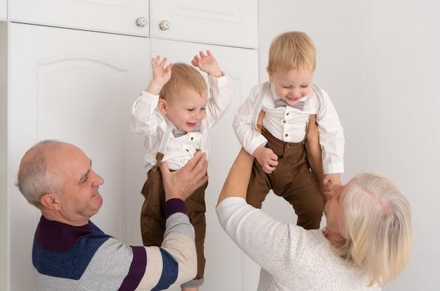 Szczęśliwy, dobrze wyglądający starszy mąż i żona z ich uroczymi wnukami bliźniakami.