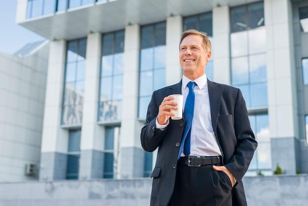 Szczęśliwy dojrzały biznesmen trzyma filiżankę kawy