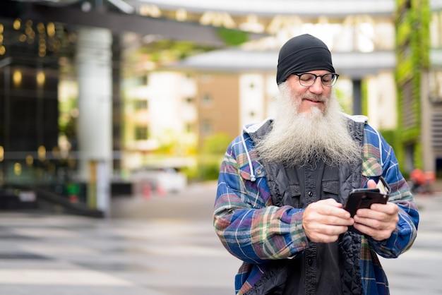 Szczęśliwy dojrzały brodaty mężczyzna za pomocą telefonu na ulicach miasta na zewnątrz