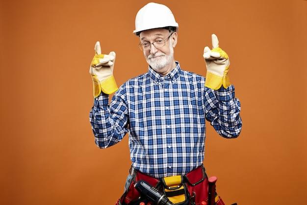 Szczęśliwy dojrzały emerytowany robotnik budowlany w żółtych gumowych rękawiczkach, torbie i białym kasku, patrząc z radosnym szerokim uśmiechem, gotowy do pracy, wskazując oba palce wskazujące w górę