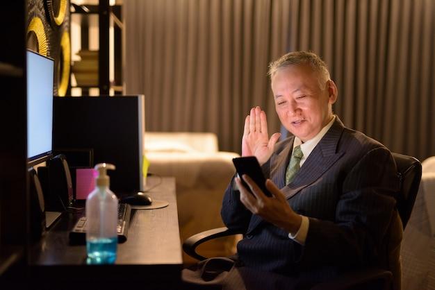 Szczęśliwy dojrzały japoński biznesmena wideo dzwoni z telefonem podczas gdy pracujący nadgodziny w domu póżno przy nocą