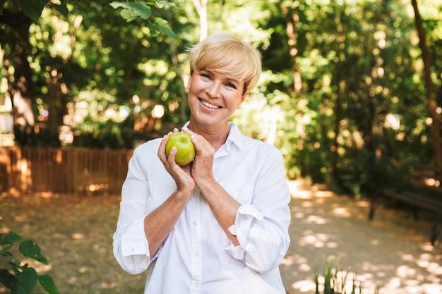 Szczęśliwy dojrzały kobiety mienia zieleni jabłko