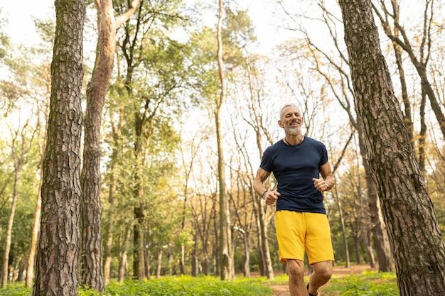 Szczęśliwy dojrzały mężczyzna cieszący się bieganiem przez las