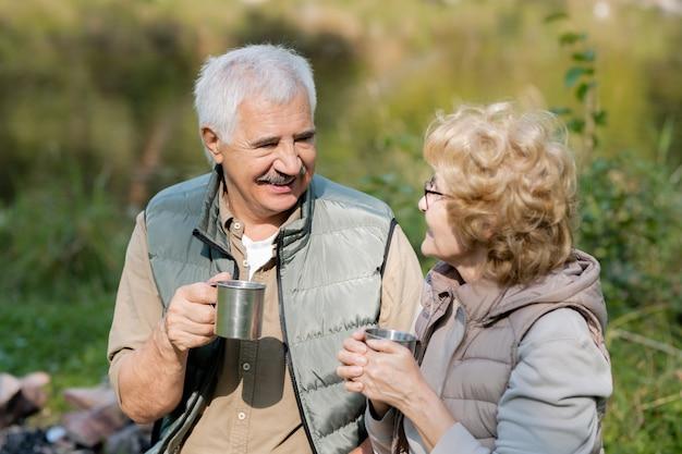 Szczęśliwy dojrzały mężczyzna i jego żona z turystycznymi kubkami patrząc na siebie podczas rozmowy w środowisku naturalnym