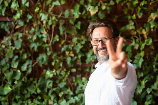 Szczęśliwy dojrzały mężczyzna noszący okulary i pokazujący znak palcami zwycięstwa stojąc przed pnączem, człowiek pokazujący znak v. portret uśmiechniętego mężczyzny pokazującego symbol pokoju przed zielonymi roślinami