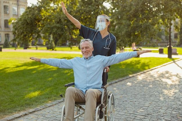 Szczęśliwy dojrzały mężczyzna odzyskujący pacjenta na wózku inwalidzkim na spacerze z pielęgniarką noszącą osłonę twarzy i