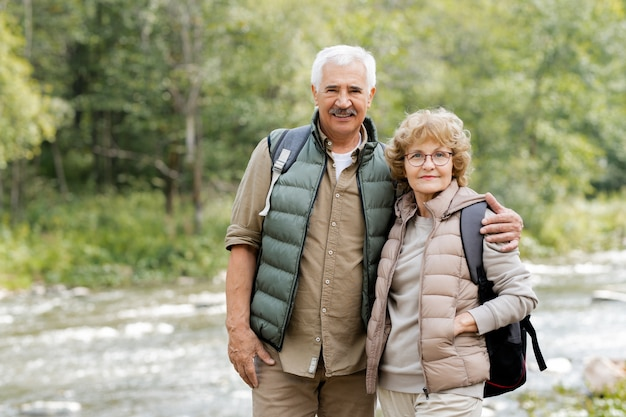 Szczęśliwy dojrzały mężczyzna turysta obejmując swoją żonę, stojąc jednocześnie przed kamerą na tle leśnej rzeki