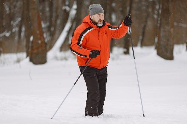 Szczęśliwy dojrzały mężczyzna w winter park. senior aktywna trekking w lesie w czasie wolnym