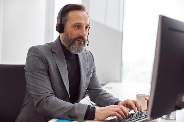 Szczęśliwy, dojrzały mężczyzna ze słuchawkami siedzi w lekkim białym biurze