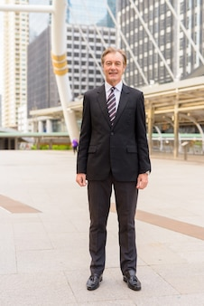 Szczęśliwy dojrzały przystojny biznesmen uśmiechając się do skywalk bridge w mieście