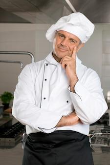 Szczęśliwy dojrzały szef kuchni patrząc na kamery i uśmiechając się w swojej restauracji