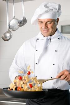 Szczęśliwy dojrzały szef kuchni stir-fry włoski makaron na patelni w restauracji