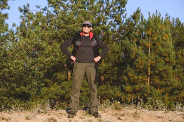 Szczęśliwy dojrzały turysta pozuje z ramionami akimbo na tle przyrody