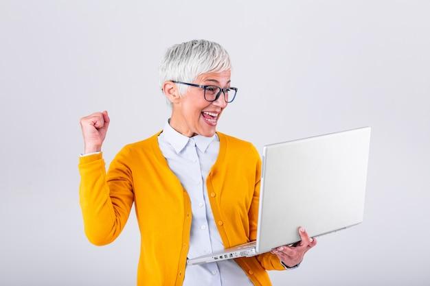 Szczęśliwy dojrzały w średnim wieku starszy biznesowej kobiety zwycięzca podekscytowany czytając dobre wieści, patrząc na laptopa