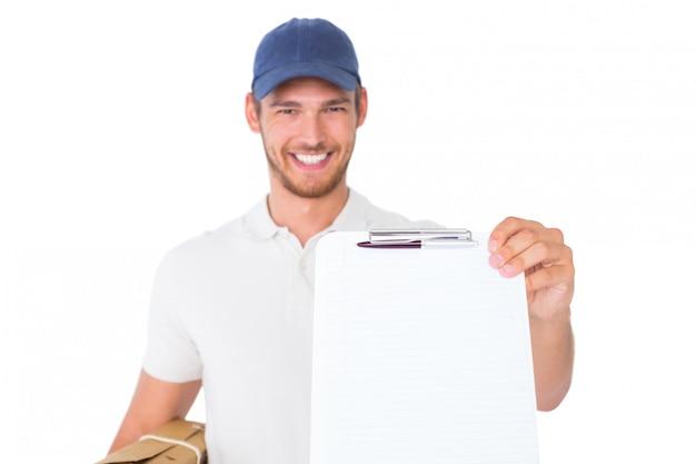 Szczęśliwy doręczeniowego mężczyzna mienia karton i schowek na białym tle
