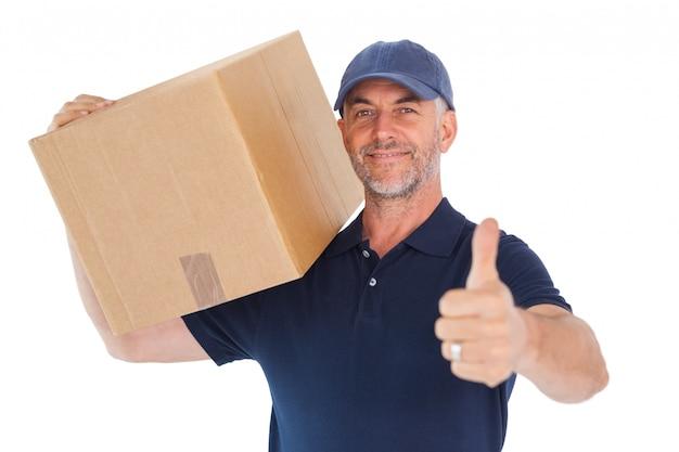 Szczęśliwy doręczeniowego mężczyzna mienia karton pokazuje aprobaty