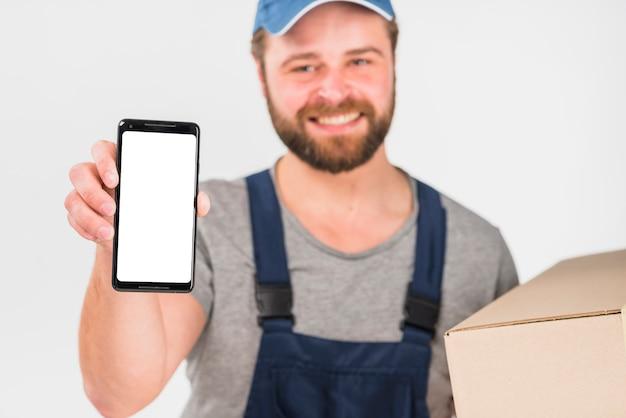 Szczęśliwy doręczeniowego mężczyzna mienia pudełko i smartphone z pustym ekranem