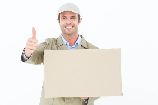 Szczęśliwy doręczeniowy mężczyzna gestykuluje aprobaty podczas gdy niosący karton